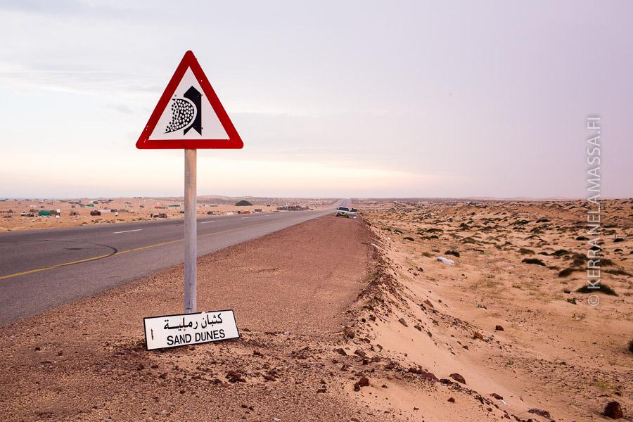Tienviitta varoittaa hiekkadyyneistä, jotka voivat tukkia teitä.