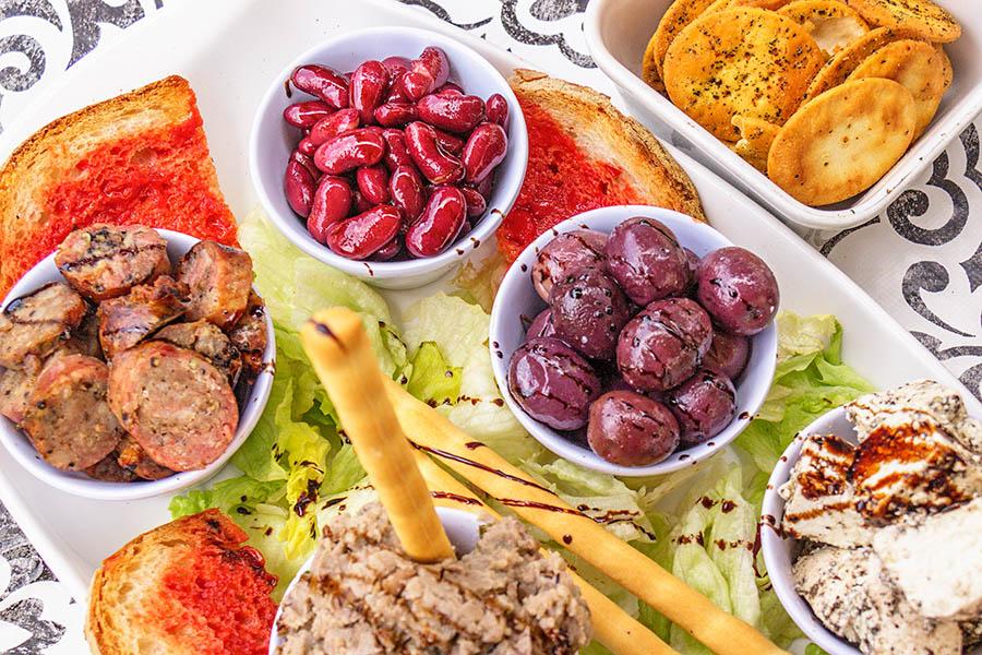 Tyypillisiä maltalaisia alkupaloja eli tomaattitahnalla voideltua leipää, maltalaista makkaraa, papuja, oliiveja, pippuroitua lampaanmaitojuustoa, aurinkokuivattuja tomaatteja (on leikattu pois kuvasta tosin) ja bigillaa eli härkäpavuista valmistettua tahnaa. Kuva: Arna Grym.