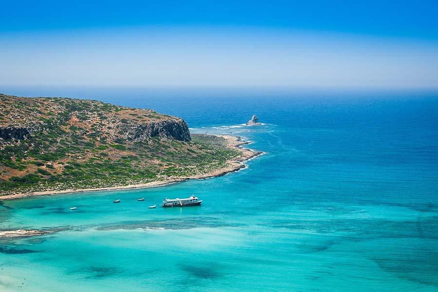 Kreetan maisemissa turkoosi meri yhtyy karuihin vuoriin ja kukkuloihin.