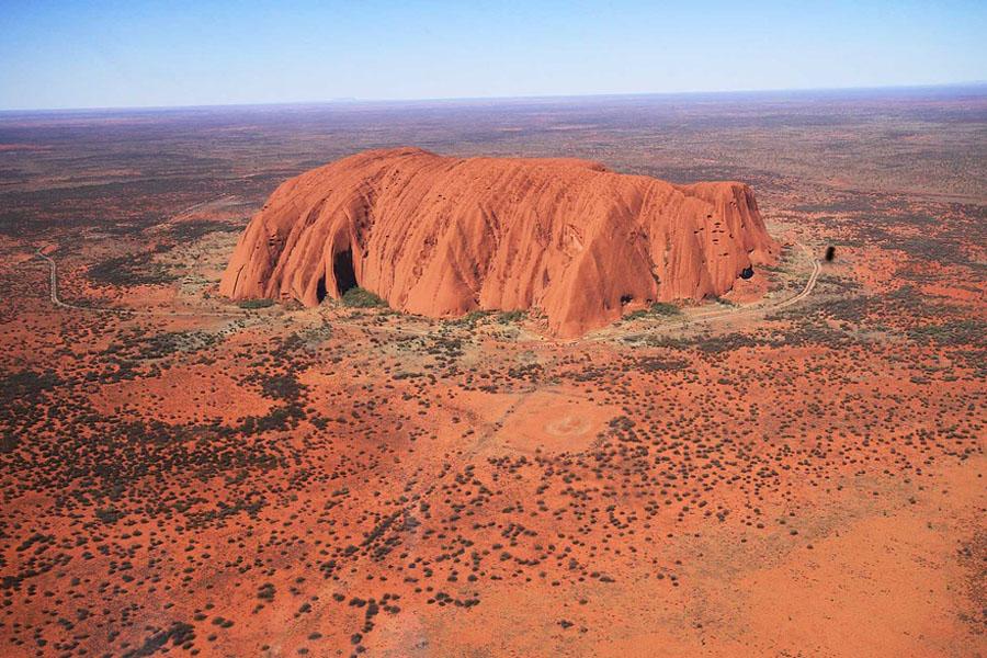 Australian aboriginaalien pyhä kivi Uluru nousee keskeltä aavaa outbackia.